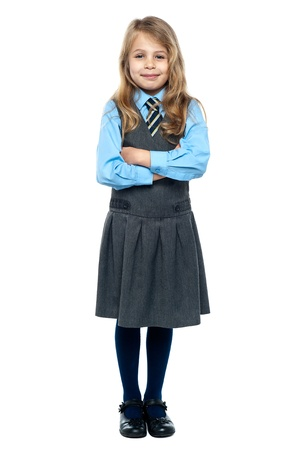 cheerfully: School girl posing for a picture cheerfully on white background.