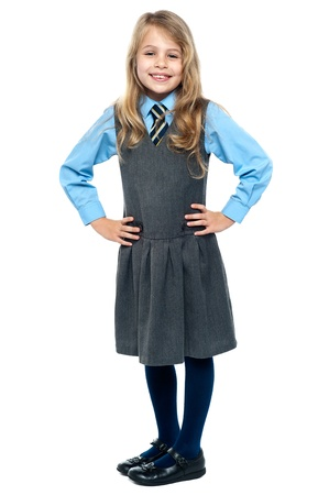 Charming kid posing with hands on waist isolated against white. photo