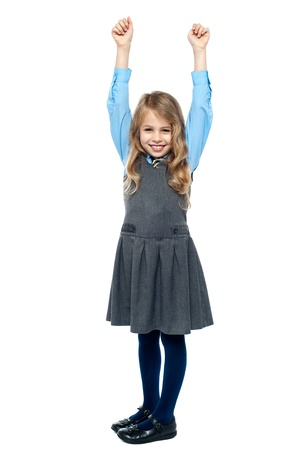 Smiling school child raising her hands in excitement. Isolated on white. photo