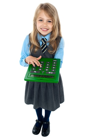 Aerial view of pretty schoolgirl in studio pressing key 6 on calculator. photo