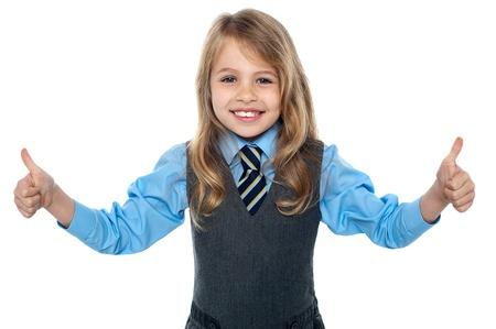 escuela primaria: Sonriendo chico joven que muestra los pulgares dobles para cámara.
