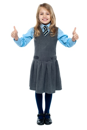 posing  agree: Charming young kid in school uniform showing double thumbs up sign.