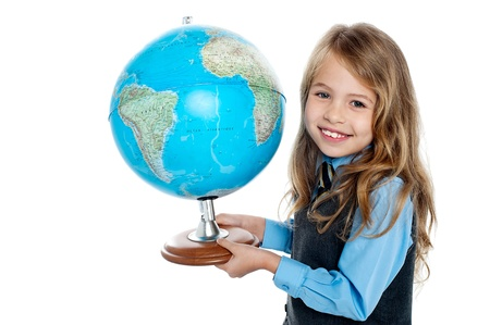 Pretty school girl kid holding globe in her hand, education concept. photo