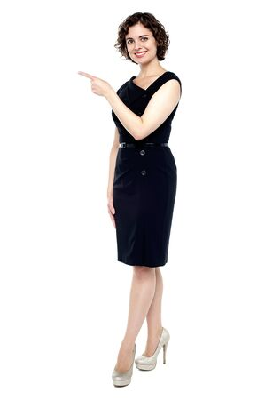 Full length shot of a fashionable woman pointing towards the copy space area. photo