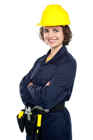 Pretty woman wearing yellow hard hat and dressed in jumpsuit. photo