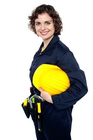 Young happy woman in construction uniform holding yellow safety helmet. photo