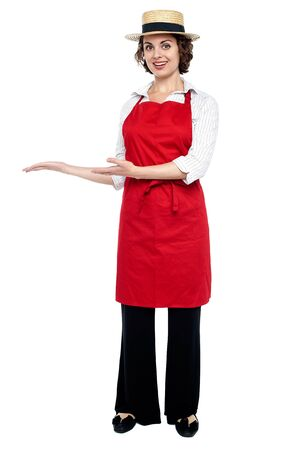 Full length portrait of a model in a bakers apron isolated against white. photo