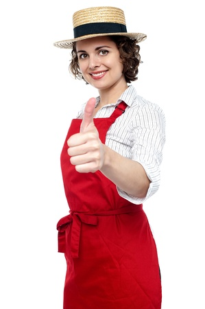 Pretty baker woman in red apron showing thumbs up gesture. photo