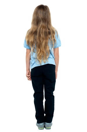 little girl posing: Rear view of a young blonde girl with long hair, full length portrait. Stock Photo