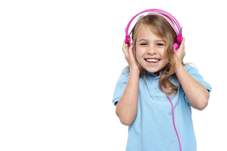 Studio shot of an excited young girl enjoying loud music, using pink headphones. photo
