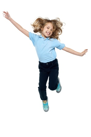 salto largo: Hermosa ni�a salta arriba en el aire, con los brazos extendidos hacia los lados. Foto de archivo
