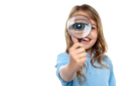 Cute little girl on white background showing her magnified eye. photo