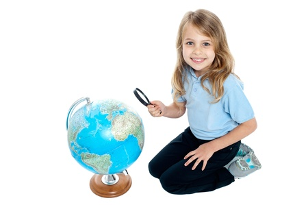 Happy young kid with magnifying glass kneeling on the floor, globe placed in front of her. photo