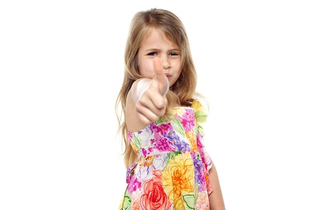 posing  agree: Charming young female kid showing thumbs up sign gesture, white background.
