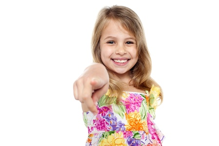 Cute little smiling blonde girl pointing finger towards the camera.