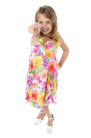 frock: Studio shot of a beautiful girl in floral designed frock pointing towards you. Stock Photo