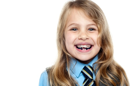 Closeup shot of a happy school kid flashing toothy smile wearing braces.