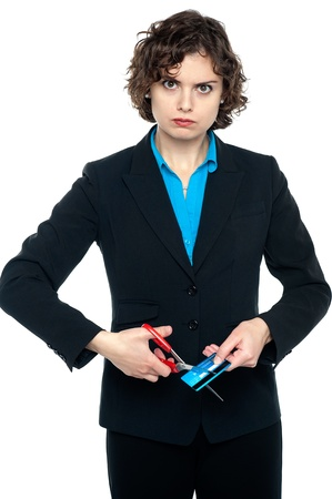Annoyed businesswoman cutting cash card, staring at the camera. photo