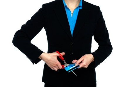 Cropped image of a woman in formals cutting credit card with scissors. photo