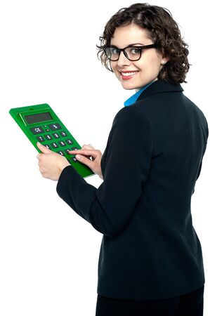 Bespectacled entrepreneur using calculator. Turning back and smiling. photo
