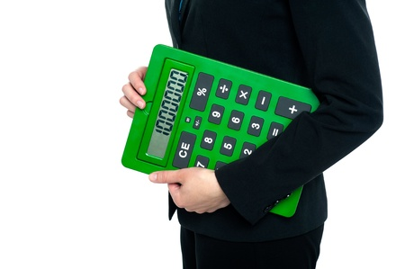 Female executive on white background posing with a large green calculator. photo