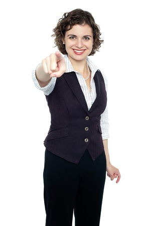 Cute young corporate lady pointing towards camera. photo