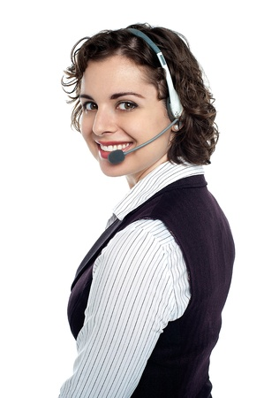 Cheerful call centre employee with headphones on turning back and smiling at the camera. Stock Photo - 17959376