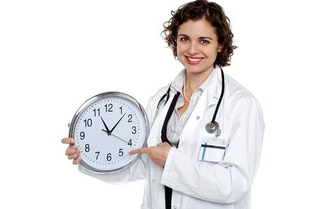 Attractive medical practitioner with a clock in hand pointing out the time. photo