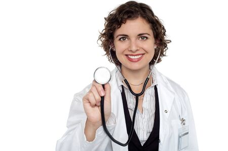 Smiling lady doctor on white is ready for consultation, showing stethoscope. photo