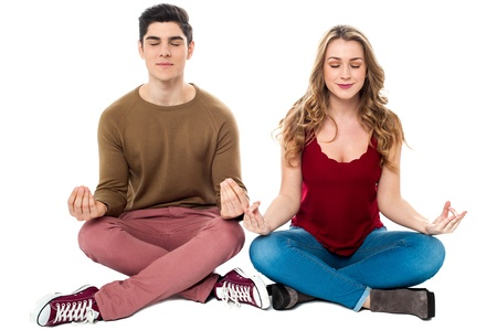 crossed legs: Young man and woman on white background meditating peacefully.