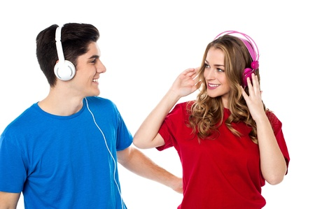 Lovely young couple with headphones on tuned into musical world. photo
