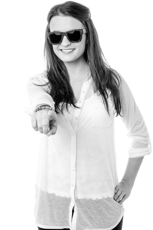 Pretty teen wearing dark shades and  pointing towards the camera. photo