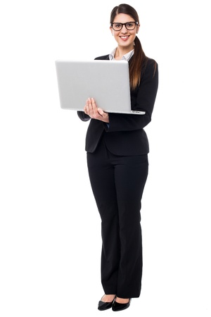 Bespectacled executive holding laptop. Full length portrait. Stock Photo - 17988827