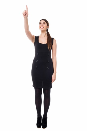 Full length portrait of a woman pointing at something specific. photo