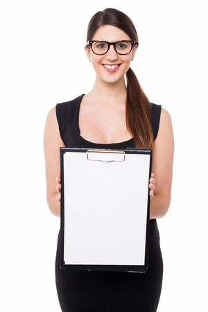 Cheerful young female displaying blank clipboard to you, white background. photo
