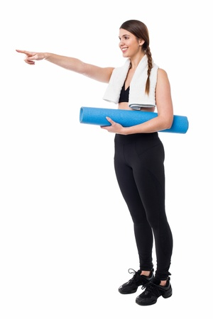 Full length portrait of a young female holding a mat and pointing forward. photo