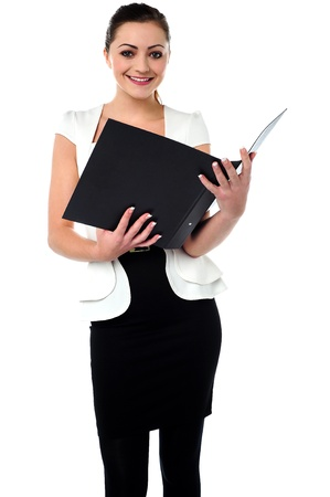 Pretty woman in trendy wear looking at the file, reviewing stats. photo