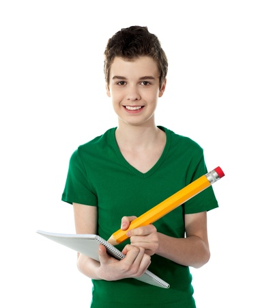 Smiling confident student taking down notes. Holding big yellow pencil. photo