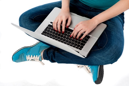 crossed legs: Female working on laptop, typing project report Stock Photo