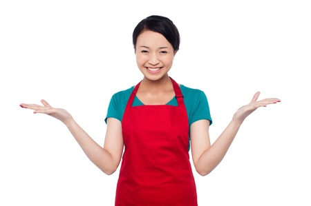 warm welcome: Young female chef standing with warm welcome gesture