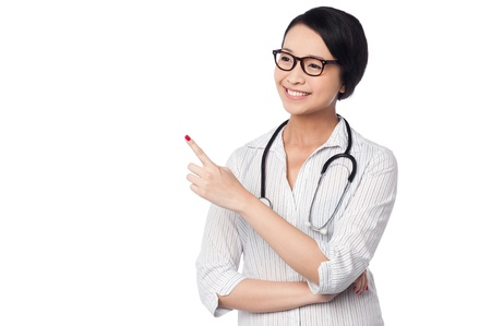 Young smiling casual female doctor looking and pointing away photo