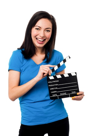 Cheerful asian young female holding clapperboard over white photo