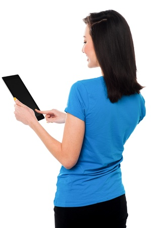 Pretty asian girl placing her finger on touch pad device while operating it. Stock Photo - 19862586
