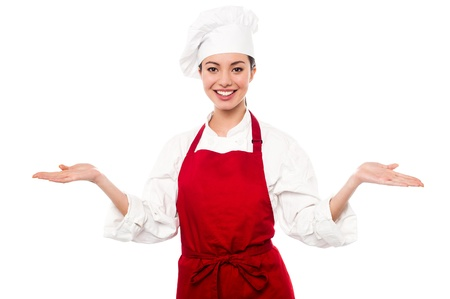 warm welcome: Smiling young female chef standing with open palms, warm welcome gesture