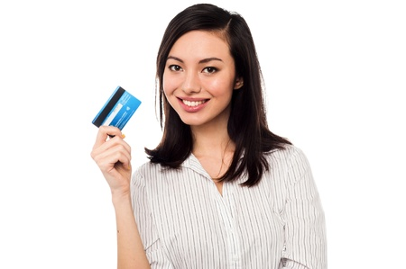 Smiling asian young female model holding up credit card photo