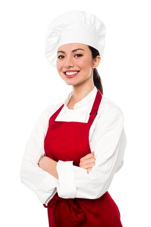 Pretty baker woman posing with confidence, arms folded photo