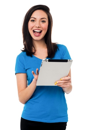 Cheerful young girl browsing on tablet device Stock Photo - 19861070