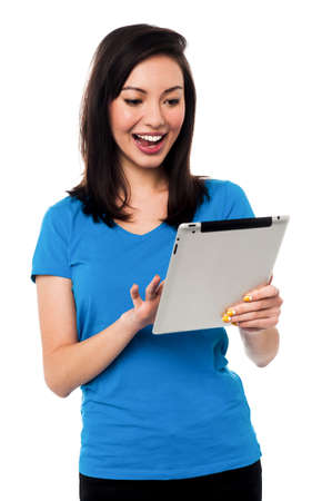 Beautiful chinese girl playing games on tablet device Stock Photo - 19861071
