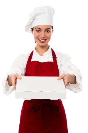 Attractive young female chef delivering pizza to the customer photo