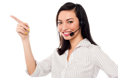 customer care: Cheerful female call center executive wearing headset and pointing away.